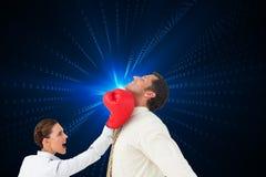 Коммерсантка ударяя бизнесмена с перчатками бокса Стоковые Фото