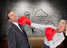 Коммерсантка ударяя коллеги с ее перчатками бокса Стоковая Фотография