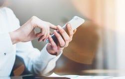Коммерсантка фото крупного плана работая офис нового startup проекта современный Современный smartphone держа женские руки и каса Стоковые Фотографии RF