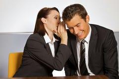 Коммерсантка шепча в ухе бизнесмена на офисе Стоковое Изображение RF