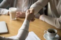Коммерсантка handshaking пар делая дело в кафе, конец вверх по v Стоковая Фотография