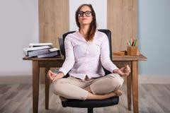 Коммерсантка meditating в офисе стоковые изображения