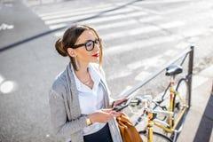 Коммерсантка outdoors с велосипедом Стоковая Фотография