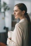 Коммерсантка Sidattractive молодая держа чашку и смотря прочь в офисе Стоковое Изображение