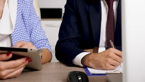 Коммерсантка swiping на цифровом экране ПК пока бизнесмен принимает примечания акции видеоматериалы