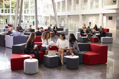 Коммерсантки встречая в занятом лобби современного офиса Стоковые Фото