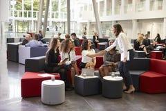 Коммерсантки встречая в занятом лобби современного офиса Стоковая Фотография