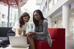 2 коммерсантки встречая в зоне лобби современного офиса Стоковое Фото
