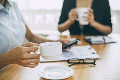 Коммерсантки выпивая кофе в офисе Стоковая Фотография RF