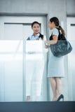 Коммерсантки готовя лифт и имея переговор стоковые изображения