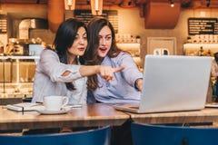 коммерсантки 2 детеныша Девушки с радостным сюрпризом показывают руку на экране компьютера, взгляд девушек на мониторе в изумлени Стоковая Фотография