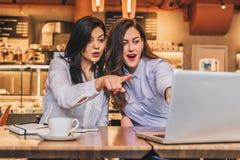 коммерсантки 2 детеныша Девушки с радостным сюрпризом показывают руку на экране компьютера, взгляд девушек на мониторе в изумлени Стоковые Изображения RF
