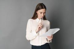 Коммерсантки держат документы в ее руке одно Изолировано на серой предпосылке стоковые фотографии rf