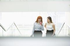 Коммерсантки имея кофе пока двигающ вверх шагает в офис Стоковое Изображение