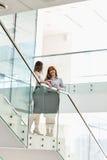 Коммерсантки имея кофе пока стоящ на шагах в офисе Стоковые Фото