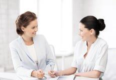 2 коммерсантки имея обсуждение в офисе Стоковое Изображение