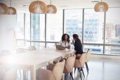 2 коммерсантки используя компьтер-книжку в встрече зала заседаний правления Стоковая Фотография