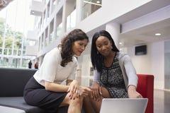 2 коммерсантки используя компьтер-книжку в лобби современного офиса Стоковые Изображения