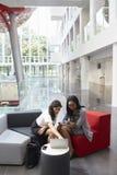 2 коммерсантки используя компьтер-книжку в лобби современного офиса Стоковое Фото