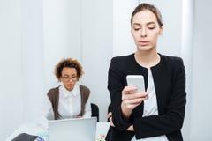 2 коммерсантки используя smartphone и компьтер-книжку в офисе Стоковое Изображение