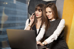 2 коммерсантки на офисе работая с компьтер-книжкой Стоковые Фотографии RF