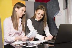 2 коммерсантки на офисе работая с компьтер-книжкой Стоковые Изображения RF