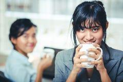 Коммерсантки на перерыве на чашку кофе в офисе Стоковые Изображения RF