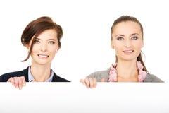 2 коммерсантки нося большую белую доску Стоковые Фото
