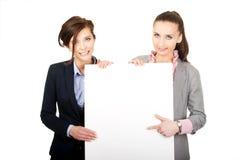 2 коммерсантки нося большую белую доску Стоковые Изображения