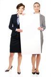 2 коммерсантки нося большую белую доску Стоковые Фотографии RF