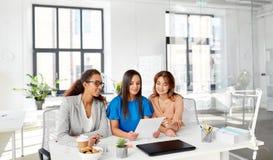 Коммерсантки обсуждая бумаги на офисе Стоковое фото RF