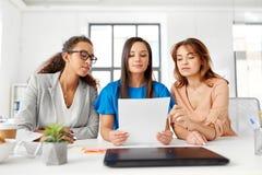 Коммерсантки обсуждая бумаги на офисе Стоковые Фотографии RF