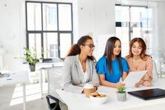 Коммерсантки обсуждая бумаги на офисе Стоковое Изображение