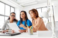 Коммерсантки обсуждая бумаги на офисе Стоковое Фото