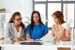 Коммерсантки обсуждая бумаги на офисе Стоковые Изображения