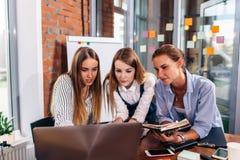 3 коммерсантки обсуждая их дело проектируют использующ компьтер-книжку совместно в офисе Стоковая Фотография RF
