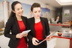 2 коммерсантки обсуждая работу в офисе Стоковое Изображение