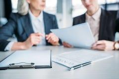 2 коммерсантки обсуждая дело проектируют на встрече в офисе, доске сзажимом для бумаги и контракте на переднем плане Стоковые Изображения