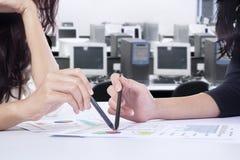 Коммерсантки обсуждая диаграмму выгоды на таблице Стоковые Фото