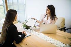 Коммерсантки обсуждая контракт и предлагают для костюма подписи на столе офиса Стоковое Фото