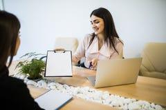 Коммерсантки обсуждая контракт и предлагают для костюма подписи на столе офиса Стоковая Фотография
