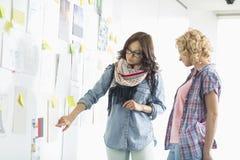 Коммерсантки обсуждая над бумагами вставили на стене в творческом офисе Стоковая Фотография RF