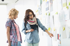 Коммерсантки обсуждая над бумагами вставили на стене в творческом офисе Стоковое Изображение RF