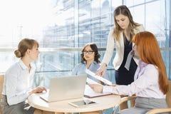 Коммерсантки обсуждая над документами на таблице в офисе Стоковое Изображение RF