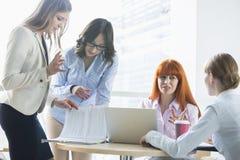 Коммерсантки обсуждая над документами на таблице в офисе Стоковое Изображение