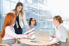 Коммерсантки обсуждая над документами на таблице в офисе Стоковое Фото