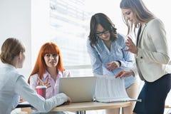 Коммерсантки обсуждая над документами на таблице в офисе Стоковые Изображения RF