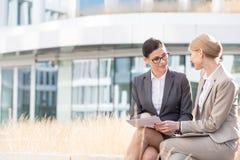 Коммерсантки обсуждая над документами пока сидящ вне офисного здания Стоковая Фотография