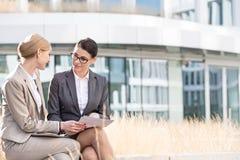 Коммерсантки обсуждая над документами пока сидящ вне офисного здания Стоковое Изображение RF