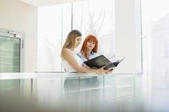 Коммерсантки обсуждая над папкой файла в офисе Стоковые Фото